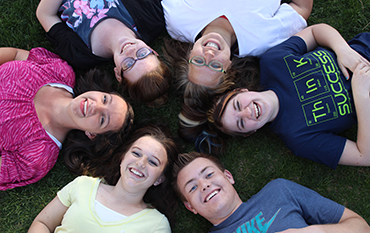 A few SUCCESS students in a circle laying on the grass with their heads together.