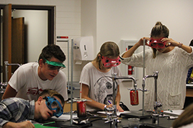 SUCCESS students doing experiements with soda cans in the science room with safety goggles on.