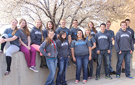 SUCCESS Academy's student government students pose in front of trees with spring buds
